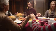 Family holding hands at Thanksgiving table and grandmother saying grace video