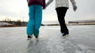 Family ice skating on frozen lake video