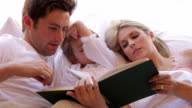 Family In Bed Reading Book Together video