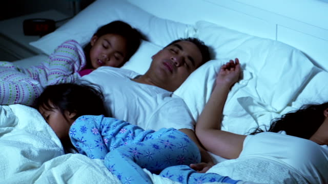 Family in bed together sleeping video
