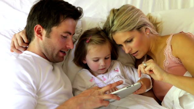 Family In Bed Using Digital Tablet video