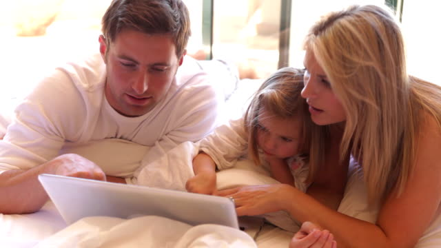 Family In Bed Using Laptop video