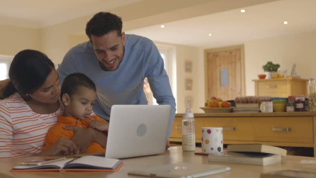 Family In Kitchen Looking At Laptop Together video