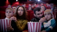 Family in the cinema eating popcorn video