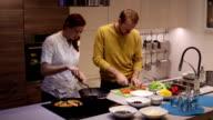 Family in the kitchen preparing dinner video