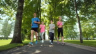 SLO MO TS Family jogging through avenue in a beautiful park video