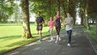 SLO MO TS Family jogging through park on sunny day video