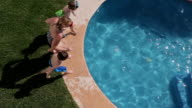 Family jumping into pool, overhead view video