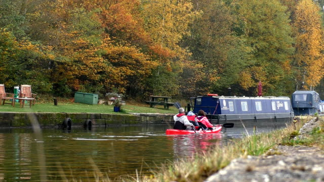 Family kayaking in autumn on the canal video