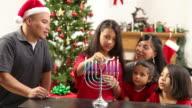 Family lighting menorah during holidays video