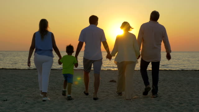 Family looking at golden sunset over the sea video