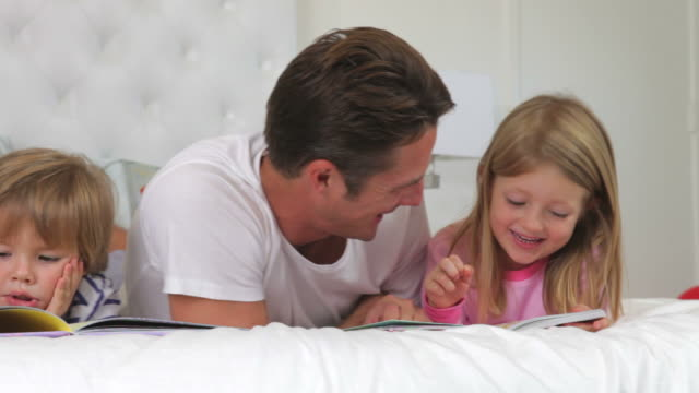 Family Lying In Bed Reading Books Together video