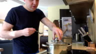 family make lunch. Father cook soup, mom baby fruit refrigerator. video