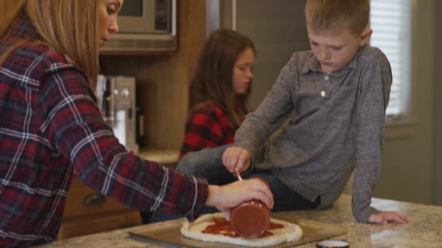 Family making homemade pizza together in the kitchen video