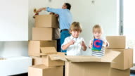 Family moving house and packing in boxes video