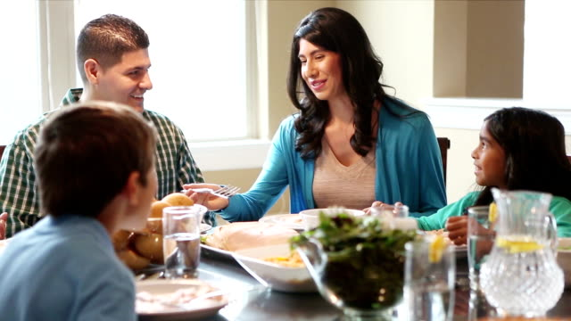 Family of four enjoying dinner together at home video