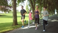 SLO MO Family of four jogging in park video