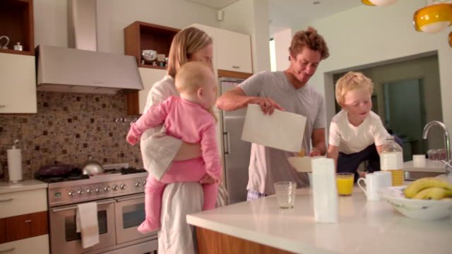 Family of Four Standing and Having Breakfast in Kitchen video