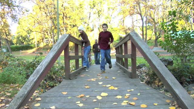 Family of four walks over a bridge video