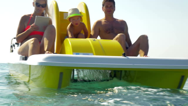 Family of three enjoying water ride on pedal boat video