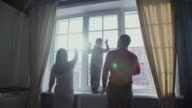 Family of three people: mother, father and child stand by the window video