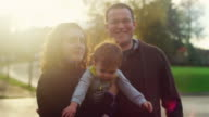 Family of three posing for a photo with lens flare, little boy trying to get away video