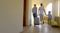 Family of three with roll-on bags in hotel video
