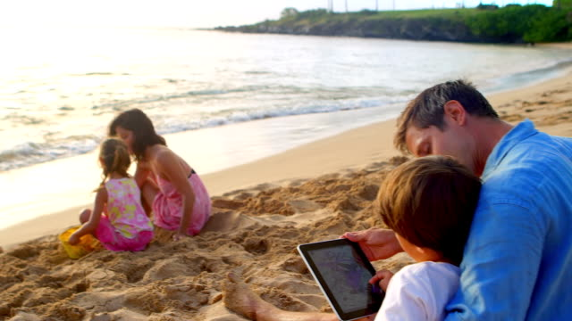 Family on a beach with computer tablet video