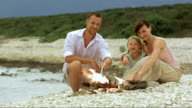 Family on beach enjoying by the fire video