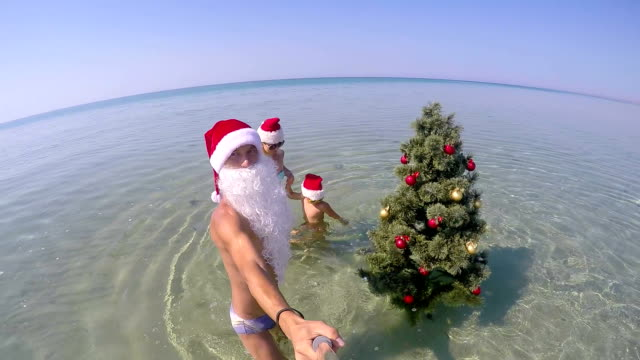 Family on beach vacation having fan dancing around the Christmas tree video