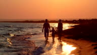 Family on beach vacation leaving afar to horizon along surf line at sunset video