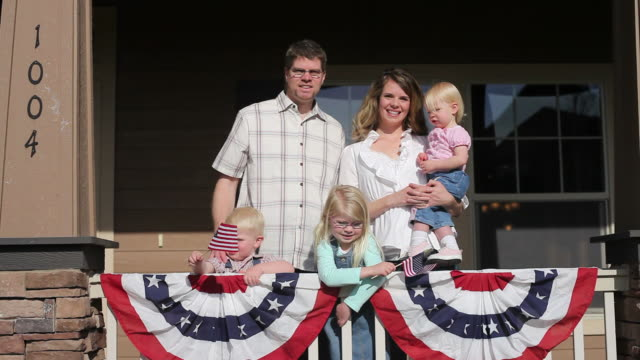 Family on porch with American flags video