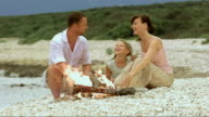 Family on white beach by the fire video