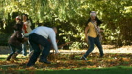 Family outdoors in Autumn throwing leaves video