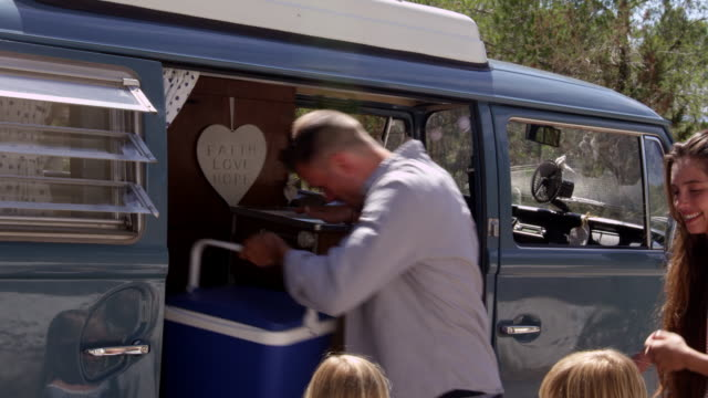 Family packing up their camper van for a road trip, shot on R3D video