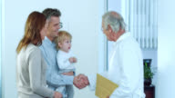 Family physician greeting the toddler with parents video