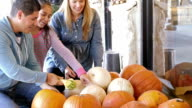 Family picking shopping for pumpkins at outdoor market stall video