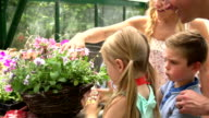 Family Planting Hanging Basket In Greenhouse video