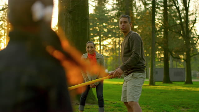 Family playing baseball in a park video