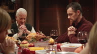 Family praying before Thanksgiving dinner video
