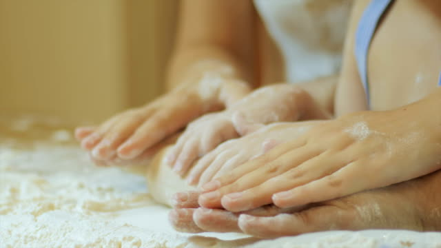 family prepares the dough on a wooden table, they knead the dough with flour, homemade pastry for bread , video