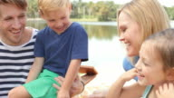 Family Relaxing As They Sit Outdoors By Lake Together video