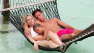 Family Relaxing In Beach Hammock video