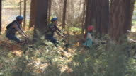 Family riding mountain bikes through a forest, panning shot video