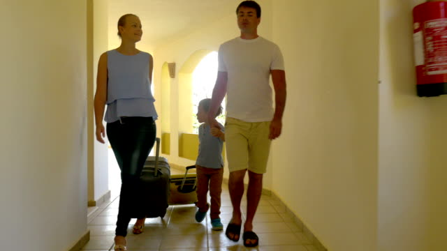 Family Rolling Trolley Bags along the Hotel Passage video
