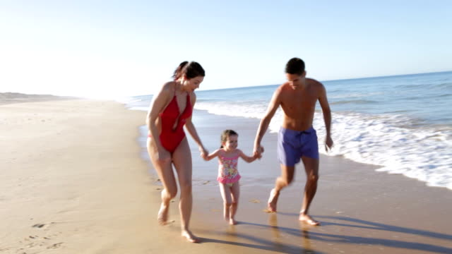 Family Running Along Beach Shoreline video