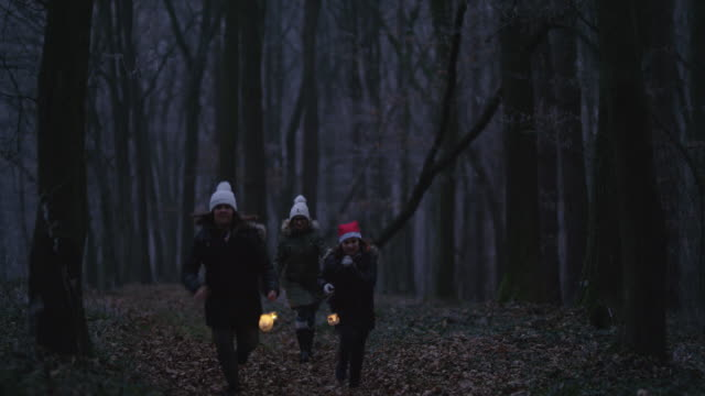 WS Family running through a forest with lanterns video