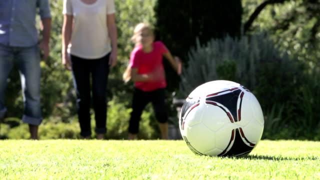 Family Running To Kick Football In Garden video