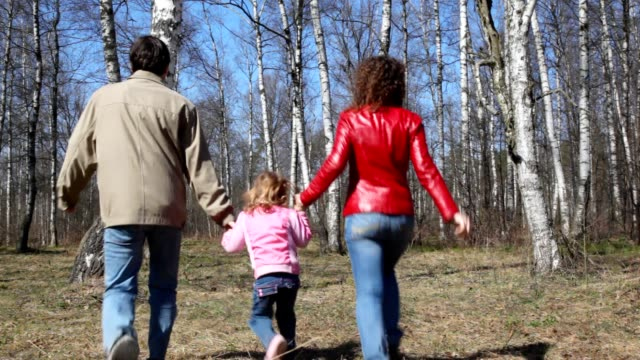Family runs from camera to spring forest video