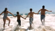Family runs into ocean together, slow motion video